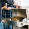 Coyote 18-Inch Portable Electric Grill On Patio Post